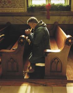 A man praying at a church at Christmas time.