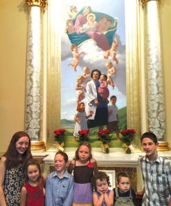 The Carstens family stands in front of the painting of St. Gianna at the Shrine of Our Lady of Guadalupe. Helen, far left, and Dominic, far right, are portrayed in the painting, standing on the left and right of St. Gianna.