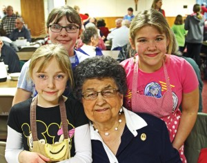 Catherine Warnecke's faith and dedication extend well beyond playing the church organ for 35 years. She's surrounded by Violet, Constance and Abigail Rusch, servers at the parish soup supper.